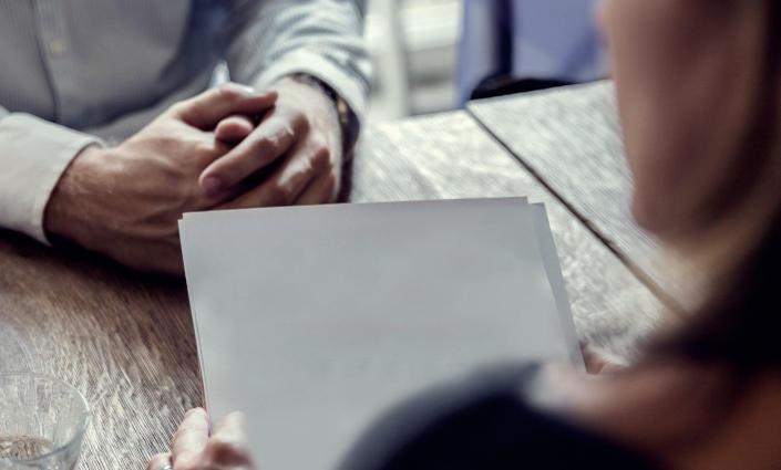 image partielle femme de dos tenant une feuille de papier, devant mains croisées du personnage en face