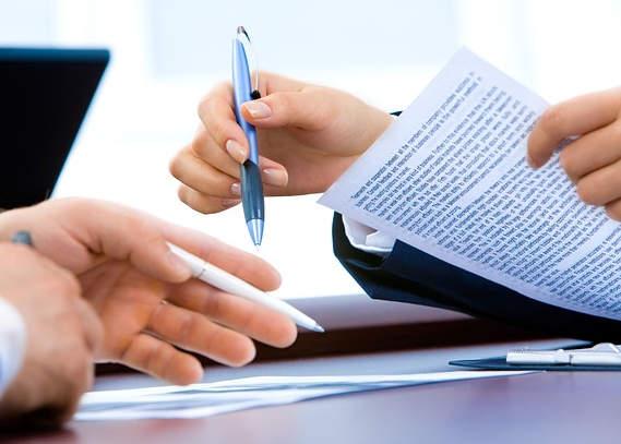 deux mains face à face tenant des stylos et une feuille de papier