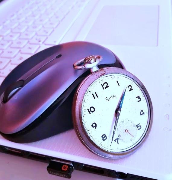 montre ancienne adossée à souris d'ordinateur posés sur un clavier blanc