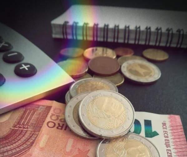 billets et pièces de monnaie euros devant carnet et morceau de calculatrice