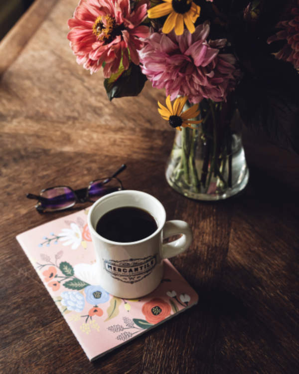 tasse à café devant bouquet de fleurs