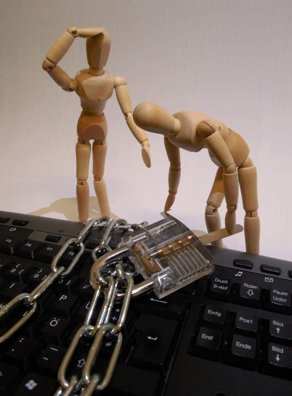 manequins en bois sur un clavier avec chaine et cadenas