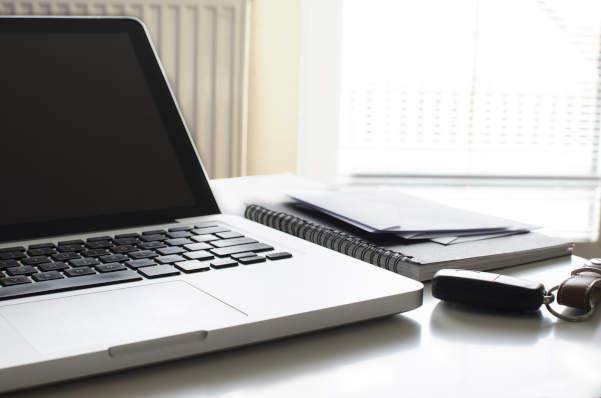 ordinateur ouvert avec carnet et clés