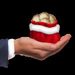main ouverte offrant de l'argent placé dans un bonnet de père noël