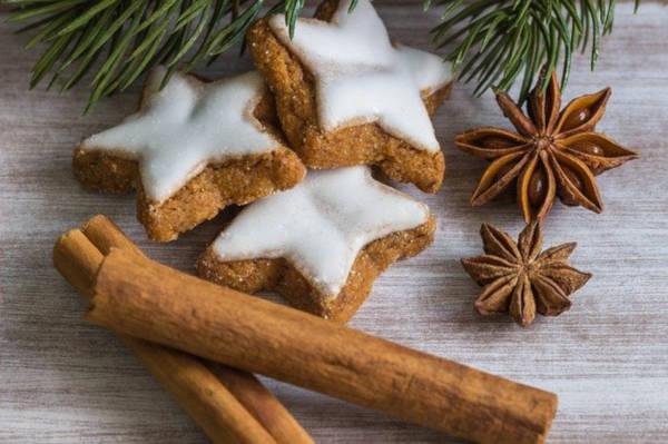 trois biscuits de noel en forme d'étoiles glacés au sucre blanc avec deux batons de canelle et de l'anis étoilé