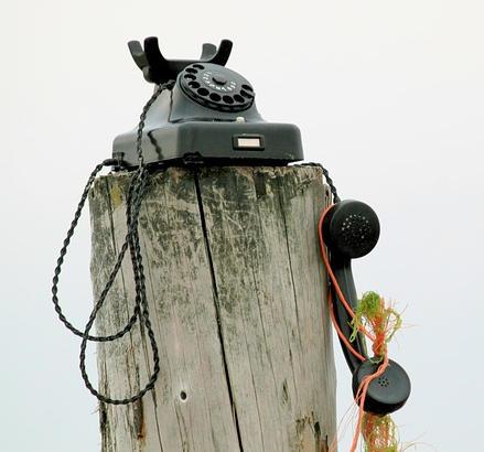 vieux téléphone décroché posé sur un piquet en bois