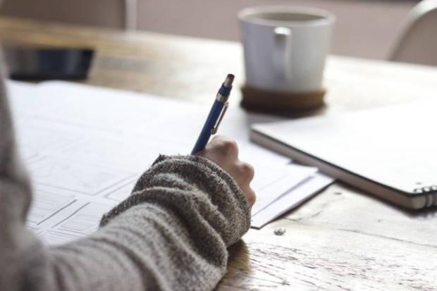 bras et main tenat un stylo en train d'écrire sur des feuilles posees sur le bureau