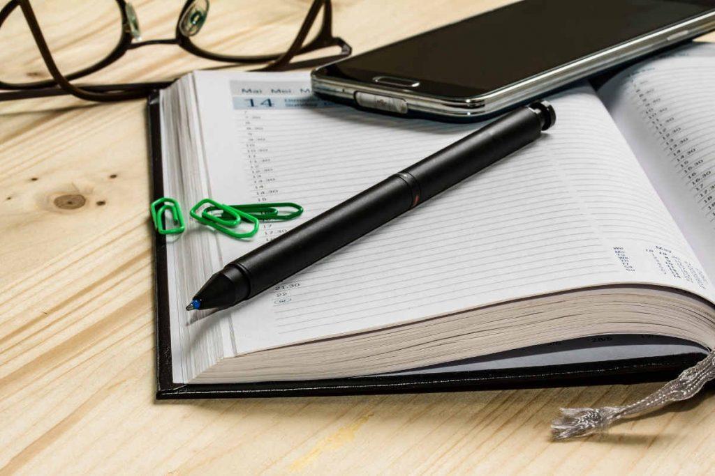 agenda ouvert page blanche avec stylo pose dessus et tel portable